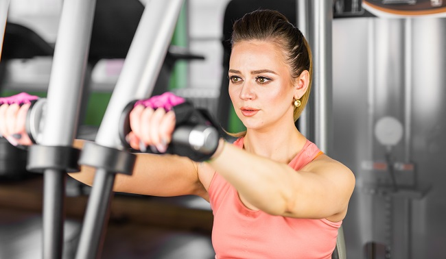 fitness, sport, powerlifting and people concept - sporty woman doing workout in gym.